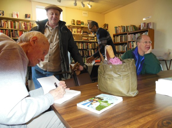 "Norman Zierold, author of ""That Reminds Me,"" autographs one of his books for Peter Ecob Saturday at Revelations Café, after a book discussion. Freddy Fonseca, center, pushes in a chair after attending Zierold's interview while Terry Weiss, seated, talks with others across the table."