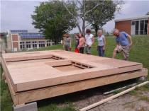 Students and volunteers raise the walls on Heather Caldwell's tiny house. / KTVO's Kate Allt