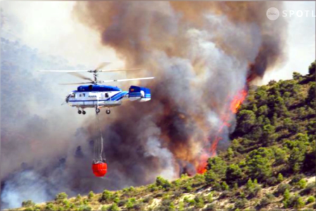 Helicopters carry water-filled Bambi Buckets to help put out forest fires copy